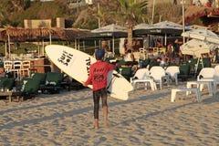Der junge Surfer, der Bretter einer Brandung auf Hertzlija hält, setzen, Israel auf den Strand Stockfotos