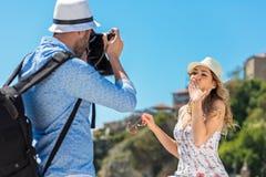Der junge touristische Mann machen Foto seines Freundinsitzens Stockbild