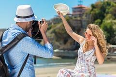 Der junge touristische Mann machen Foto seines Freundinsitzens Lizenzfreie Stockbilder