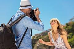 Der junge touristische Mann machen Foto seines Freundinsitzens Stockfoto