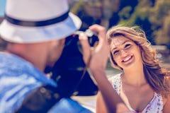 Der junge touristische Mann machen Foto seines Freundinsitzens Lizenzfreies Stockfoto
