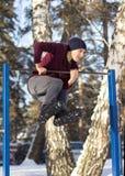 Der Junge tut Übungen auf einer horizontalen Stange Stockfotos