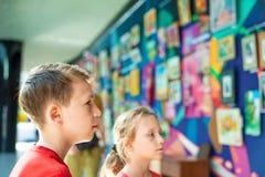 Der Junge und das Mädchen an der Ausstellung von Malereien und von Fotografien aufmerksam betrachtet die Malerei und genießt die  Stockbilder