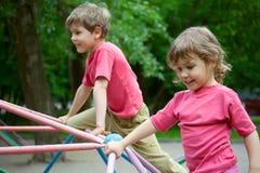 Der Junge und das Mädchen spielen einen Spielplatz der Kinder Stockfotos