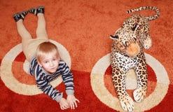 Der Junge und der Spielzeugleopard auf dem Teppich stockfotografie