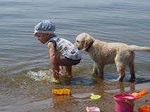 Der Junge und der Welpe, die im Fluss spielen Lizenzfreie Stockbilder