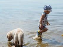 Der Junge und der Welpe, die im Fluss spielen Lizenzfreies Stockfoto