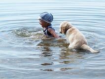 Der Junge und der Welpe, die im Fluss spielen Stockfotografie