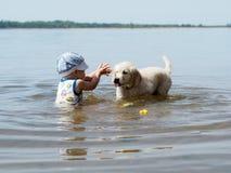 Der Junge und der Welpe, die im Fluss spielen Stockfotos