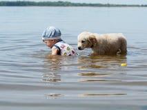 Der Junge und der Welpe, die im Fluss spielen Lizenzfreies Stockbild