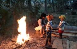 Der Junge und ein Mann wärmten sich durch das Feuer Lizenzfreie Stockfotografie