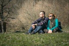 Der Junge und Mädchen, die auf dem Gras im Park und stationieren und genießen stockfotos
