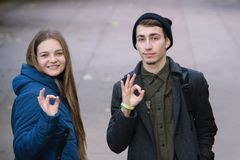 Der Junge und Mädchen, die auf weißem Hintergrund darstellen, übergeben OKAYzeichen lizenzfreie stockfotografie