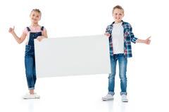 Der Junge und Mädchen, die leere Fahne halten und darstellen, greift herauf Zeichen ab lizenzfreie stockfotos