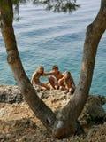 Der Junge und zwei Mädchen umfaßt durch das Meer Stockfoto