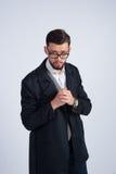 Der junge unrasierte Mann in einem schwarzen Mantel stockfotografie