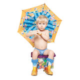 Der Junge unter einem Regenschirm sitzt auf einem Kasten stockfotografie