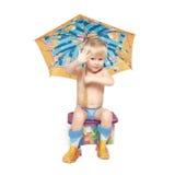 Der Junge unter einem Regenschirm sitzt auf einem Kasten Lizenzfreie Stockbilder
