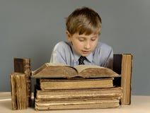 Der Junge verbringt Zeit alte Bücher lesend Lizenzfreies Stockbild