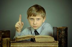 Der Junge verbringt Zeit alte Bücher lesend Lizenzfreie Stockfotografie