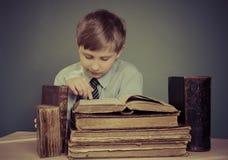 Der Junge verbringt Zeit alte Bücher lesend Lizenzfreie Stockbilder