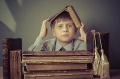 Der Junge verbringt Zeit alte Bücher lesend Stockbilder