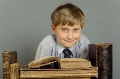 Der Junge verbringt Zeit alte Bücher lesend Lizenzfreies Stockfoto