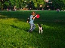 Der Junge von 8-9 Jahren bildet den Hund aus Lizenzfreies Stockfoto