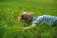 Der Junge von 8-9 Jahren liegt auf einer Rückseite im dichten grünen Gras Lizenzfreie Stockbilder