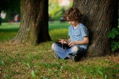 Der Junge von 8-9 Jahren sitzt unter einem großen Baum mit Tablette auf Schoss Lizenzfreie Stockbilder