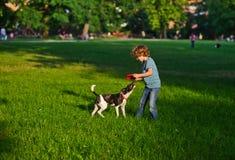 Der Junge von 8-9 Jahren spielt zusammen mit dem Hündchen auf einem grünen Gras im Park Stockbilder