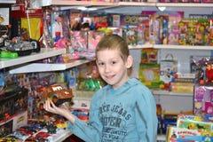 Der Junge wählt ein Spielzeug im Spielzeugsladen Stockfotos