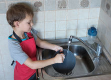 Der Junge wäscht Teller Stockbild