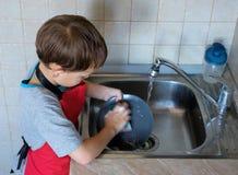 Der Junge wäscht Teller Stockfotografie