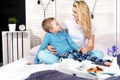 Der Junge wacht Mutter auf und gibt ihr einen Blumenstrauß von Blumen im Bett Feiern des Tages der Frau Mutter`s Tag lizenzfreie stockbilder