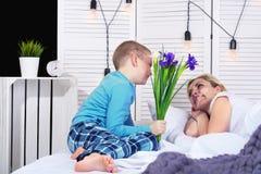 Der Junge wacht Mutter auf und gibt ihr einen Blumenstrauß von Blumen im Bett Feiern des Tages der Frau Mutter`s Tag lizenzfreie stockfotos