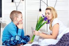 Der Junge wacht Mutter auf und gibt ihr einen Blumenstrauß von Blumen im Bett Feiern des Tages der Frau Mutter`s Tag lizenzfreies stockfoto
