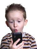 Der Junge war überrascht, im Telefon zu schauen Stockfotografie