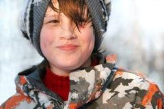 Der Junge war, lächelnd schwitzend und im kühlen Wetter Lizenzfreie Stockbilder