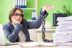 Der junge weibliche Angestellte beschäftigt mit der laufenden Schreibarbeit verkettet an den Schreibtisch stockbild