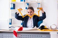 Der junge weibliche Architekt, der im B?ro arbeitet stockfotos