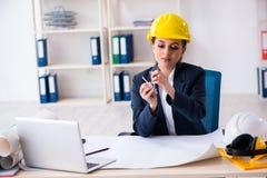 Der junge weibliche Architekt, der im B?ro arbeitet lizenzfreie stockbilder