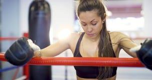 Der junge weibliche Boxer, der bei ihren Armen auf dem Ring liegt, ropes Lizenzfreie Stockfotos