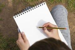 Der Junge wird ein Schwarzes und einen gelben Bleistift in einem offenen Notizbuch zeichnen lizenzfreies stockbild