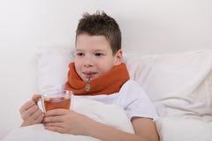 Der Junge wird mit warmen Kräutern, Recht im Bett behandelt lizenzfreie stockfotografie