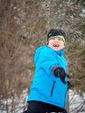 Der Junge wirft einen Schneeball lizenzfreie stockfotografie