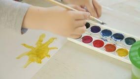 Der Junge zeichnet eine Bürste und malt die Sonne stock footage