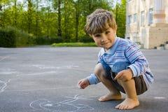 Der Junge zeichnet mit Kreide Stockfotografie