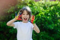 Der Junge zeigt seine bunten Hände Stockfotos