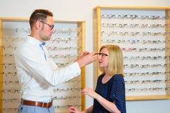 In der jungen Frau des Optikergeschäftes, die neue Gläser vorwählt Stockbild
